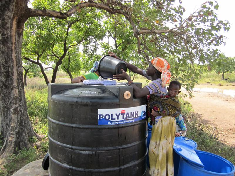 woman with child filling water conditioning tank